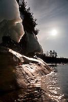 Lake Superior sea kayaker explores icy shoreline in spring on Michigan's Upper Peninsula.