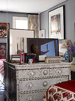 The Syrian chest of drawers in the bedroom displays photographs by John Hall (left) and Tuca Reinés, an antique Chinese mask, and an Indian inlaid box