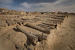 A Siwan cemetery of shallow sand graves covered by palm logs, at the base of the 13th century mud-brick fortress of Shali in Siwa Town of the Siwa Oasis, near the Libyan border in Egypt.