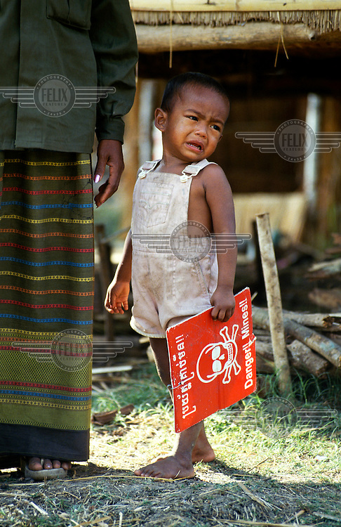 Crying child holding a 'Danger! Mines!' sign in a village heavily seeded with landmines during the years of civil war.