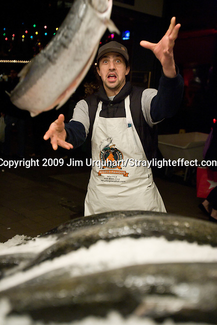 Jim Urquhart/Straylighteffect.com Fish monger Jaison Scott throws a fish at the Pike Place Fish Market at the Pike Place Market in Seattle, Washington. 12/22/2009 - Jim Urquhart/Straylighteffect.com