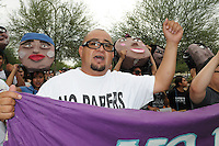 """Phoenix, Arizona (July 28, 2012) - About three hundred people marched to protest the second anniversary of the approval of some provisions of the SB 1070 immigration law. The march, called """"No Papers, No Fear"""" was organized by immigrant rights groups who say the law discriminates people of brown skin. In this photograph, protester and undocumented immigrant Miguel Guerra helps hold a banner as the """"No Papers No Fear"""" march begins in Phoenix. Guerra was arrested for a civil disobedience act on July 24 for blocking a major intersection in Downtown Phoenix. Photo by Eduardo Barraza © 2012"""