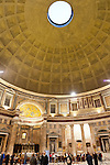 Visitors crane their necks to peer up at the amazing symmetrical dome soaring high over the open center of the Pantheon (Rome, Italy).  The dome is penetrated by the famous oculus, helping in daytime to illuminate the arches and bays below.  The imperial Roman Pantheon (built by Hadrian, dedicated by Marcus Agrippa) is among the world's tallest free-standing domes constructed from unreinforced concrete.
