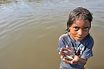 A girl displays small fish she caught in a river near Santa Paula, a hot and isolated village in northwestern Nicaragua.