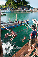 Pulau Batudaka, Togean Islands, Central Sulawesi, Indonesia. Sea gypsie children. The Bajau Sea Gypsies one roamed the seas as nomads. Nowadays they live an empoverished life of fishing and collecting trepang sea cucumbers from their stilted villages. In the 1990's they started cyanide and dynamite fishing causing major damage to the reefs and their future fish stocks. The Togean or Togian Islands are an archipelago of 56 islands and islets, in the Gulf of Tomini, off the coast of Central Sulawesi, in Indonesia. The dark green of the islands and the cristal clear water is a perfect setting and has attracted many travellers during the last years. Travellers endure the long journey in search of the mythical beach paradise. Photo by Frits Meyst/Adventure4ever.com