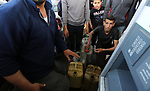 Palestinians wait to fill containers with fuel at a petrol station in Khan Younis in the southern Gaza Strip April 27, 2017. Photo by Ashraf Amra
