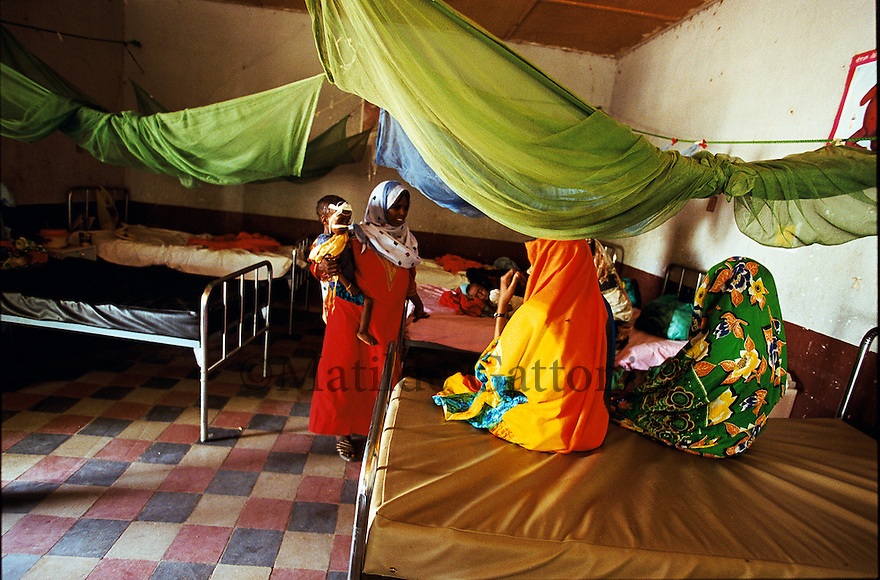 Eritrea - Gash Barka - Mothers taking care of their kids suffering mostly from severe malnutrition at the hospital. As a result of 30 years of war for independence against Ethiopia (from 1961 to 1991) and another 3 years from 1997 to 2000, there are 50,000 Eritreans currently living in internally displaced (IDP) camps throughout the country. These IDPs have fled three times in the last 10 years, each time because of renewed military conflict. They lived in relatives' homes when lucky enough, but mostly, the fled to the mountains, where they attempted to do what Eritreans do best, survive. Currently there is no Ethiopian occupation in Eritrea, but landmines prevent the IDPs from finally going home. .It is estimated that every Eritrean family lost two or three members to the war which makes the reality of the current emergency situation even more painful for Eritreans worldwide. Currently, the male population has been decreased dramatically, affecting the most fundamental socio-economic systems in the country. Among the refugee population, an overwhelming majority of families are female-headed, severely affecting agricultural production. For, IDPs in particular, 80% of households are female-headed..The unresolved border dispute with Ethiopia remains the most important drawback to Eritrea's socio-economic development, as national resources (human and material) continue to be prioritized for national defense. Eritrea is vulnerable to recurrent droughts and variable weather conditions with potentially negative effects on the 80 percent of the population that depend on agriculture and pastoralism as main sources of livelihood. The situation has been exacerbated by the unresolved border dispute, resulting in economic stagnation, lack of food security and increased susceptibility of the population to various ailments including communicable diseases and malnutrition..