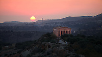 General view of the Temple of Concord, 5th century BC, and surrounding landscape, Agrigento, Sicily, Italy,  pictured on September 11, 2009, against a dramatic sunset. Well preserved owing to its 6th century AD conversion to a church, the Temple of Concord is a typical example of optical correction whose tapering columns create the illusion of a perfectly aligned building. The Valley of the Temples is a UNESCO World Heritage Site. Picture by Manuel Cohen.
