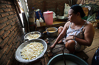 A woman cooking crisps in her home, Makassar, Sulawesi, Indonesia.  The crisps are sold later.
