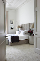 The large double bed in this sophisticated and modern bedroom features a taupe velvet upholstered headboard