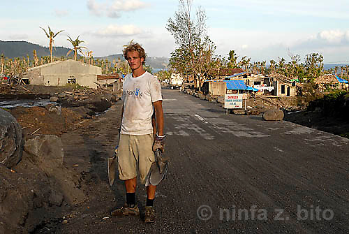 13 FEBRUARY 2007 - SANTO DOMINGO, ALBAY/PHILIPPINES - Englishman Fergus Worthy, a volunteer with Hands On Disaster Response (HODR), stands by the roadside flanked by boulders and lahar deposited by flood waters from Typhoon Durian (Reming). HODR, a US-based volunteer group for disaster response and relief, has been in the area since Boxing Day 2006 to assist the community in cleaning up and rebuilding in the aftermath of Typhoon Durian (Reming).