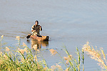 subsistance fisher rowing his dugout canoe, Caia, Zambezi River Floodplain, Sofala Province, Mozambique
