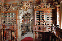 Bookcases with Chinese motifs, lacquer and gilding by Manuel da Silva, in the Red Room of the Joanina Library, or Biblioteca Joanina, a Baroque library built 1717-28 by Gaspar Ferreira, part of the University of Coimbra General Library, in Coimbra, Portugal. Through the archway is the Black Room. The Casa da Livraria was built during the reign of King John V or Joao V, and consists of the Green Room, Red Room and Black Room, with 250,000 books dating from the 16th - 18th centuries. The library is part of the Faculty of Law and the University is housed in the buildings of the Royal Palace of Coimbra. The building is classified as a national monument and UNESCO World Heritage Site. Picture by Manuel Cohen