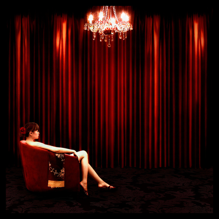 A young woman sitting in a red armchair by red curtains with a chandelier