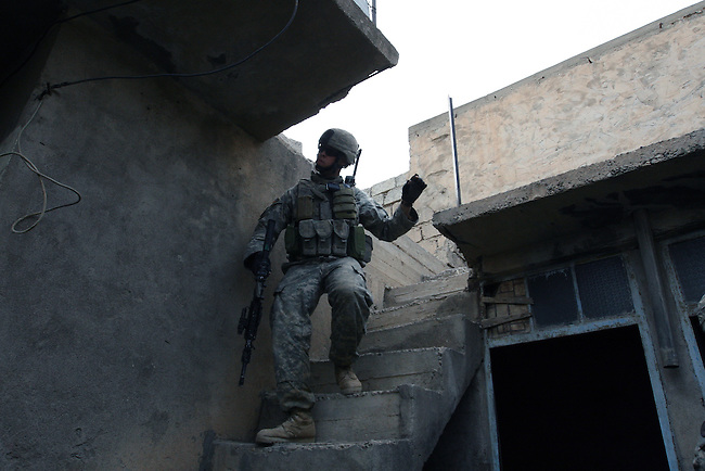 Sgt. Jonathan Jenson, 22, of Hudson, Ohio, ducks as he comes down a staircase during a patrol with Iraqi troops in Mosul, Iraq. Jenson is a soldier with Troop H, 3rd Squadron, 3rd Armored Cavalry Regiment. U.S. commanders say a string of new combat outposts and daily patrols by U.S. and Iraqi forces are pushing insurgents out of the city. March 1, 2008. DREW BROWN/STARS AND STRIPES