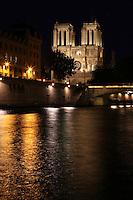 Western Facade of Notre Dame de Paris at night, seen from the quai Saint Michel, 1163 - 1345, initiated by the bishop Maurice de Sully, Ile de la Cite, Paris, France. The Small Bridge on the right. Picture by Manuel Cohen