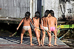 South America, Brazil, Amazon. A group of young girls enjoy playing by the river together and cooling off in the water.