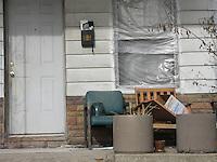 Detroit: downtown,il centro città. L'ingresso di una vecchia casa. La finestra è coperta con del cellophane. Due sedie di fronte alla porta.