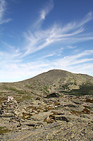 Mount Washington with blue skies and fair weather clouds over head. Mount Washington is the tallest peak in the norteastern United States at 6,288 feet tall, and is home to some of the world's worst weather.