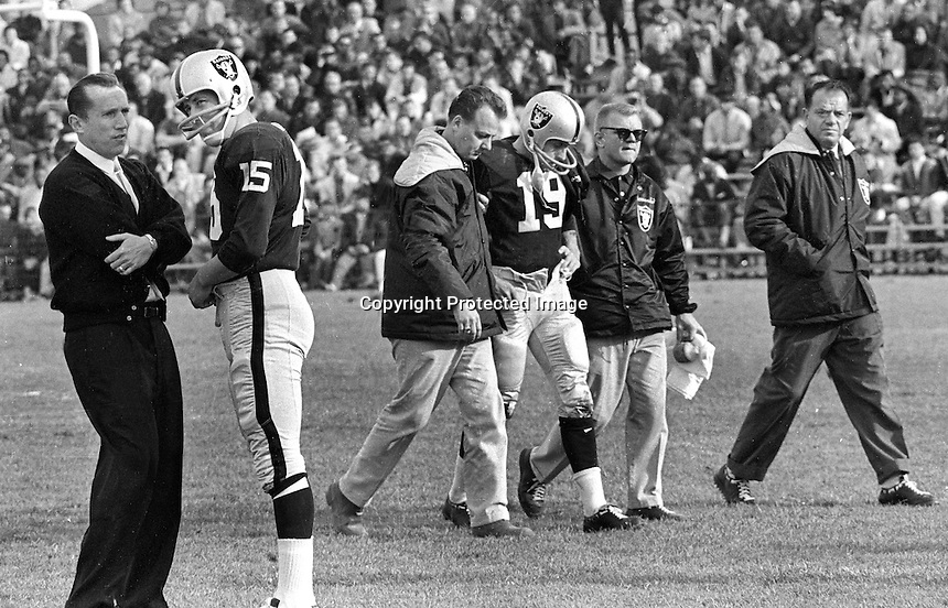 1964 Oakland Raiders...coach Al Davis talking to his quarterback Tom Flores who is going to replace #19 Cotten Davidson who is injured. Trainer George Anderson and equipment man Dick Romanski.<br />