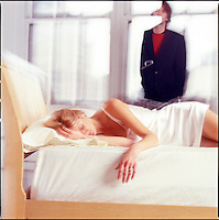 Woman in bed with man in background against windows