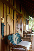 Comfortable rattan sofas line the deep wooden veranda of this beach house