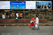 Bus shelters are most commonly used for advertisement hoardings. Here passengers are seen waiting for a bus under the Reliance Mobile advertisement.