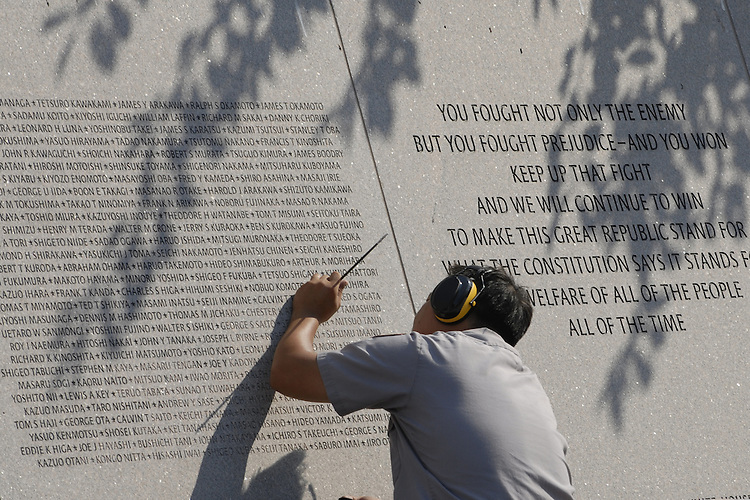 Binh Nguyen applys dye to the names on the National Japanese American Memorial to make them stand out. The National Japanese American Memorial to Patriotism was designed by Davis Buckley Architects and Planners. A memorial wall of pink granite includes inscriptions of the names of the ten World War II relocation camps and the number of people interned in each. Additional panels contain quotations commemorating patriotism and honor, as well as acknowledgement of and apology for injustices suffered. A peaceful water pool, containing several large boulders, is designed in the Zen style, while a haunting memorial bell, designed by sculptor Paul Matisse, recalls traditional Japanese temple bells. For its striking artistic beauty, this memorial has been awarded several architectural honors.