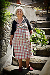 Photo of an old woman in a garden with flowers in Amalfi, Italy.