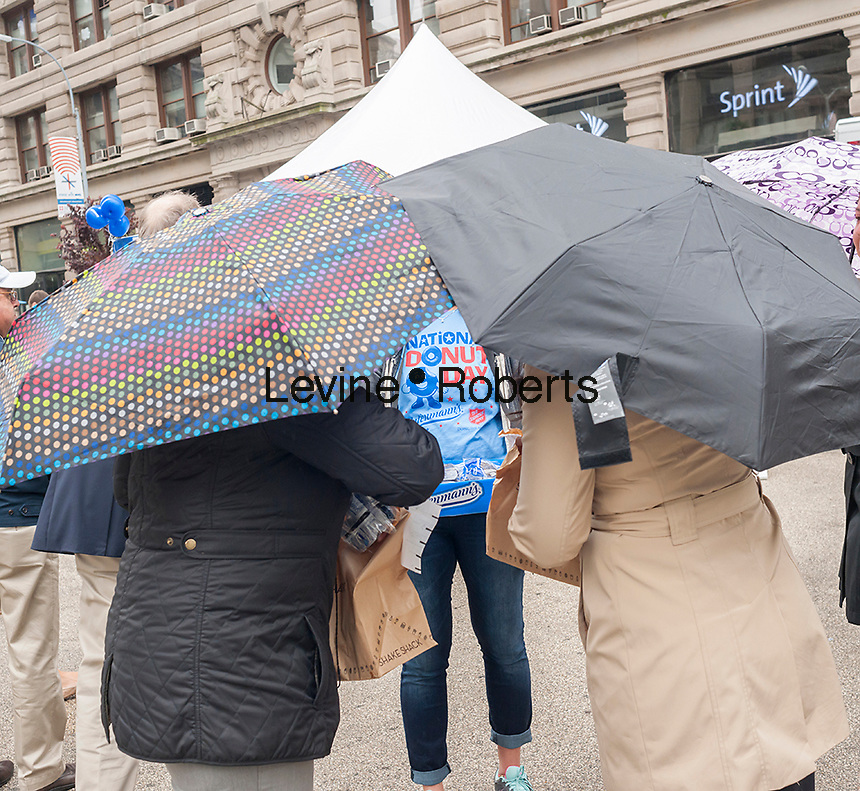 """Thousands of donut lovers flock to Flatiron Plaza in New York to celebrate  National Donut Day on Friday, June 5, 2015. Supported by Entenmann's, the bakers gave out 40,000 chocolate donuts and donated $30,000 to the Salvation Army. National Donut Day, the first Friday in June, was created in 1938 by the Salvation Army to honor the """"donut lassies"""" who administered treats and solace to soldiers during WW1. Entenmann's is a division of Bimbo Bakeries USA. (©  Richard B. Levine)"""