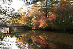 Wooden pedestrian bridge over the Ipswich River with fall colors