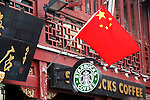 Asia, China; Shanghai. A Starbucks cafe contrasts sharply with it's surroundings - traditional Chinese architecture of the Yu Gardens in Shanghai.