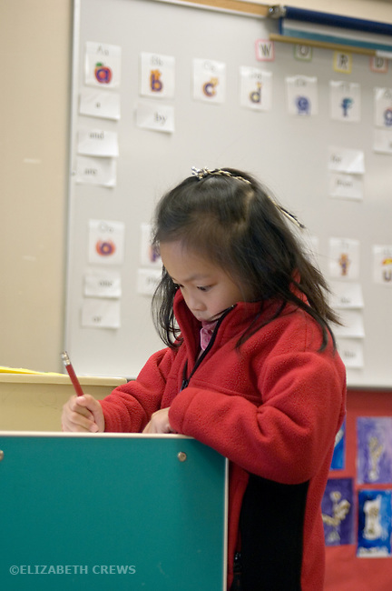 Alameda CA Kindergarten student signing herself in to class in morning