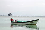 A local fisherman works on his boat in Costa Maya Mexico. The ship in the background is the Celebrity Lines Zenith...Caribbean, Mexico, water, fisherman, boat