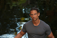 portrait of a man in a wet tee shirt by a pond in Florida
