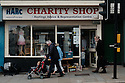 People walking past HARC Charity Shop, London Road, St Leonards-On-Sea, East Sussex.