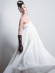 Fashion portrait of a beautiful young woman with creative hairstyle wearing a long white flying dress