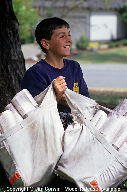 Young boy (9-10 yrs old) deliverying news papers on his route sitting under tree, Bothell, Washington USA  MR.