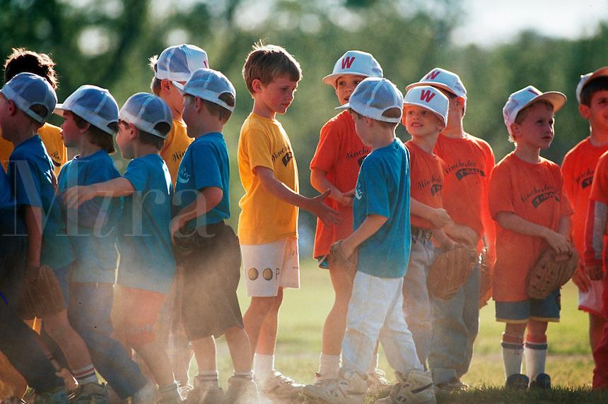 Youth baseball teams shake hands after a tee ball game.