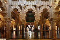 View from the maqsura, a richly decorated ribbed vault with small dome in front of the mihrab, redecorated under Al-Hakam II in 961, with intricately carved interlacing fluted arches, in the Cathedral-Great Mosque of Cordoba, in Cordoba, Andalusia, Southern Spain. Beyond the maqsura is the area of hypostyle prayer hall built under Al-Hakam II in the 10th century. The first church built here by the Visigoths in the 7th century was split in half by the Moors, becoming half church, half mosque. In 784, the Great Mosque of Cordoba was begun in its place and developed over 200 years, but in 1236 it was converted into a catholic church, with a Renaissance cathedral nave built in the 16th century. The historic centre of Cordoba is listed as a UNESCO World Heritage Site. Picture by Manuel Cohen