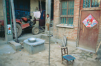 China. Province of Henan. Village Nan Laoguanzui. A young  child runs down the stairs. The boy was kidnapped in the village of Shifeng in Shaanxi province on may 12 2002, sold to a family in the village of Nan Laoguanzui. The police found him and brought him back to his family on march 4 2004. The family has then decided, because of the poverty they live in, to resell his child to the family which already bought him (from the thieves) and with whom he lived happy for almost two years. The boy plays in the courtyard of his new house. © 2004 Didier Ruef