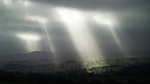 Dark rural scenery with strong rays of sunlight shining through clouds onto fields in England