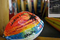A vividly painted coconut stands as an Aloha style welcome matt in a local surf shop on Oahu's north shore.
