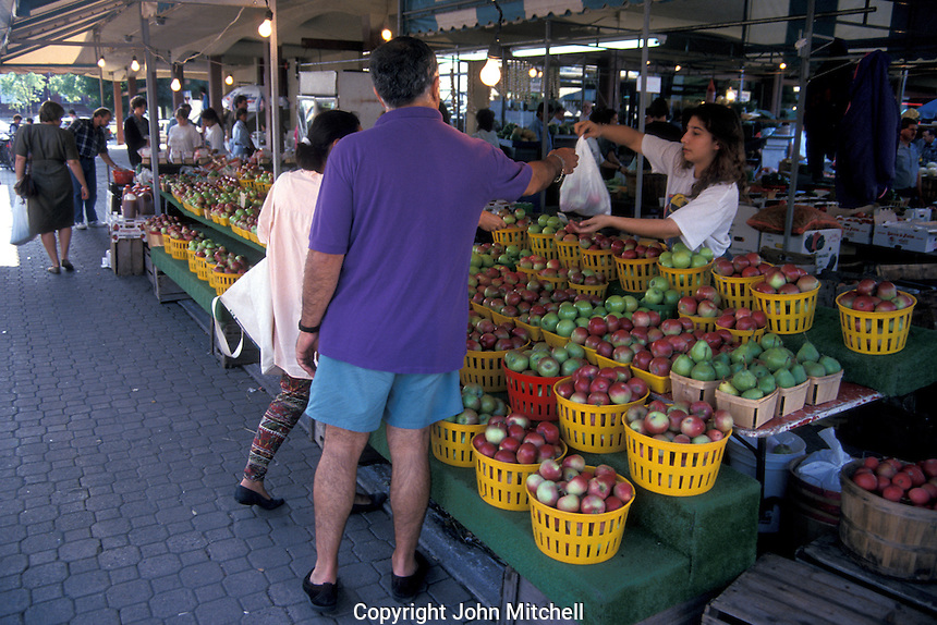 People buying apples at a fruit stand in the Atwater Market, Montreal, Quebec, Canada