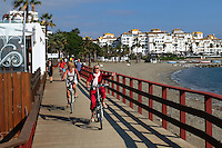 Cyclists on boardwalk between Puerto Banus &amp; San Pedro de Alcantara. Puerto Banus is in the background. November 2015. 201511121799<br />