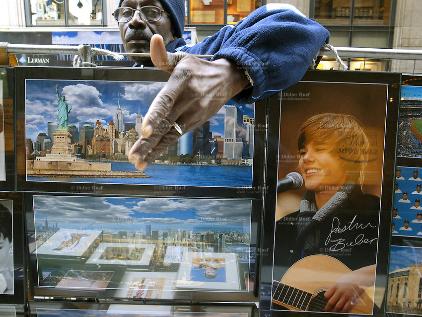 USA. New York City. An afroamerican man sells in the streets various color framed posters from the Statue of Liberty and New York skyline, and a signed picture of Justin Bieber smiling during a concert. 21.10.2011 © 2011 Didier Ruef