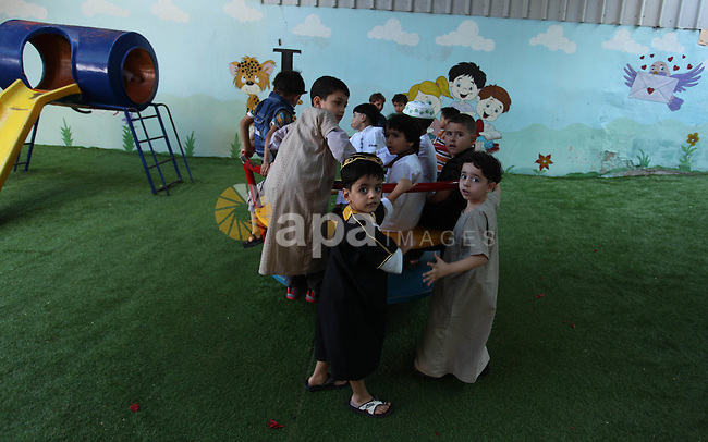Palestinian children gather around a makeshift cube representing the holy Kaaba, in Gaza, on Sept. 10, 2016, as part of training children how to perform Hajj pilgrimage. Muslims from around the world flood Saudi city of Mecca to perform the annual Hajj pilgrimage, which is one of the five pillars of Islam. Photo by Ashraf Amra