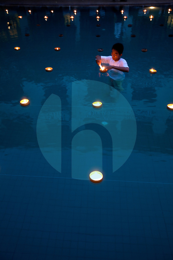 January 20th, 2009_PHNOM PENH, CAMBODIA_ Workers at the Raffles Hotel Le Royal in Phnom Penh, place candles in the hotel's swimming pool, in preparation of a wedding.  Photographer: Daniel J. Groshong/Tayo Photo Group