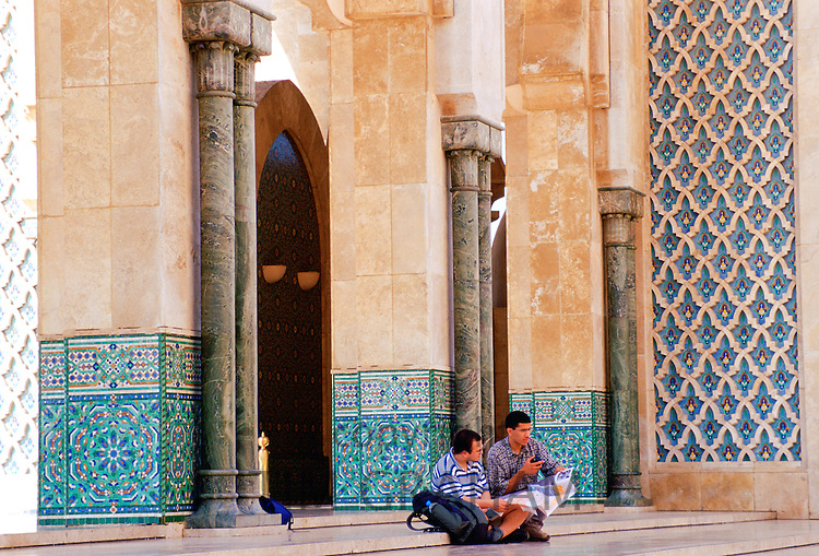 Tourists sitting on the steps of King  Hassan II Mosque in Casablanca, Morocco