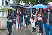 Santa Monica College students take cover under their umbrellas while waiting for the bus on Pico Blvd on Monday, December 12, 2011.
